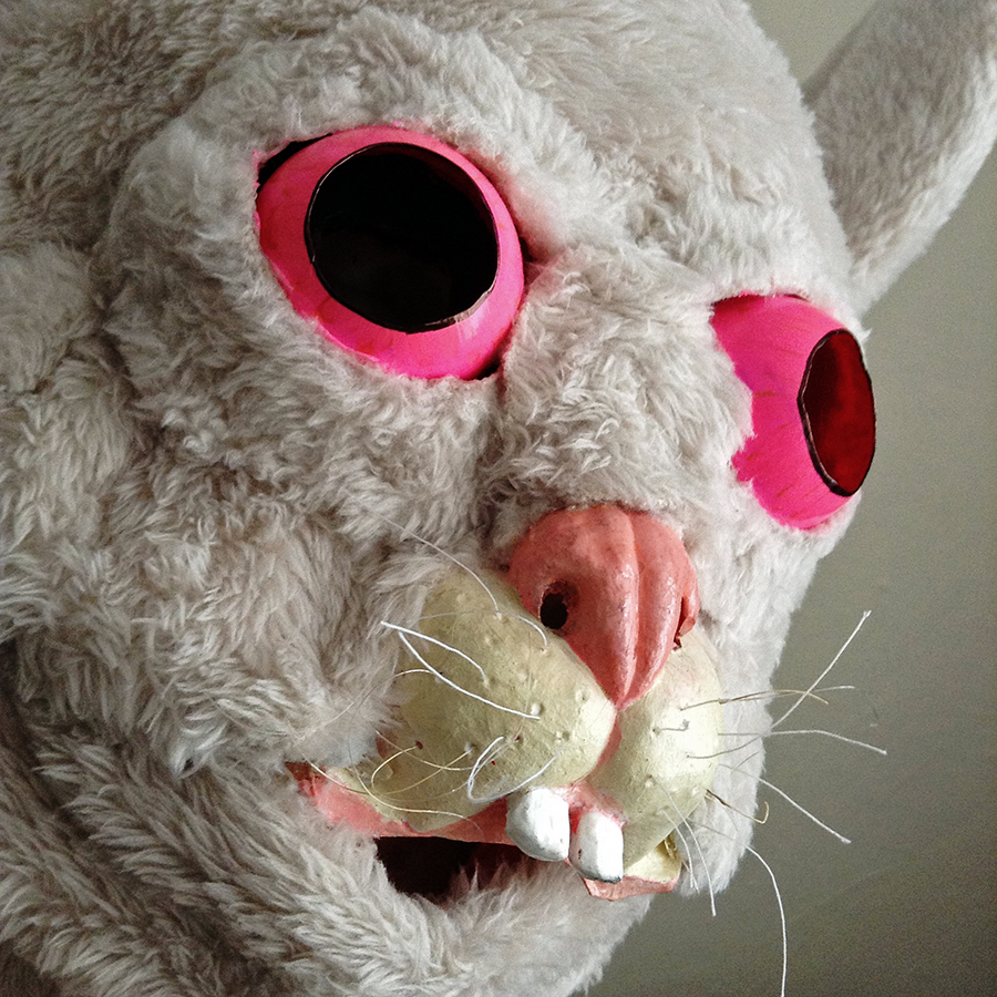 A close up of a white rabbit mask with a pink nose, whiskers, and bulbous pink eyes.