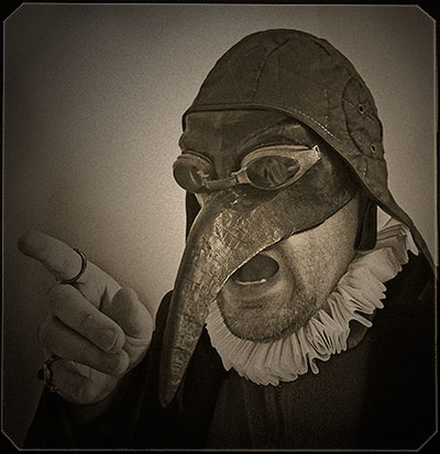 Alistair Gentry wearing a cap with long ear flaps, a plague mask with a long pointed nose, and an Elizabethan starched ruff.