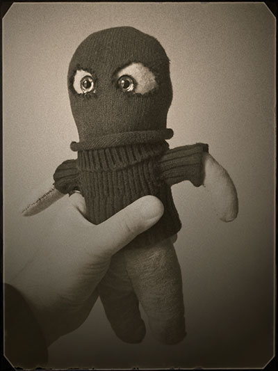 A stuffed toy that resembles a stereotypical terrorist, with a black wool balaclava and staring eyes.