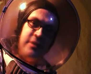 Alistair Gentry Nowhere Plains: he is in orbit above Mars, wearing a space suit with a clear bubble helmet.
