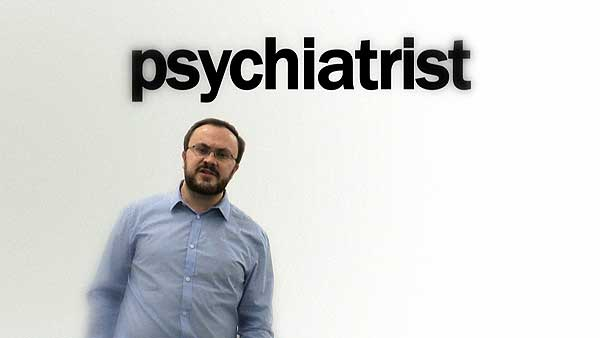 "Alistair Gentry in Stendhal Syndrome: he is standing in a blank white studio, wearing a pale blue shirt. The word ""psychiatrist"" appears in large black letters above him."