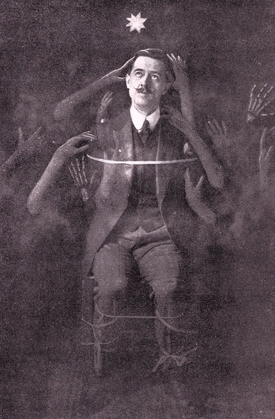 A monochrome photo of a man tied to a chair, dressed in a suit. Disembodied hands are touching him and reaching for him.