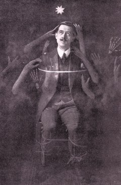 Edwardian magician William Marriott surrounded by ghost hands.