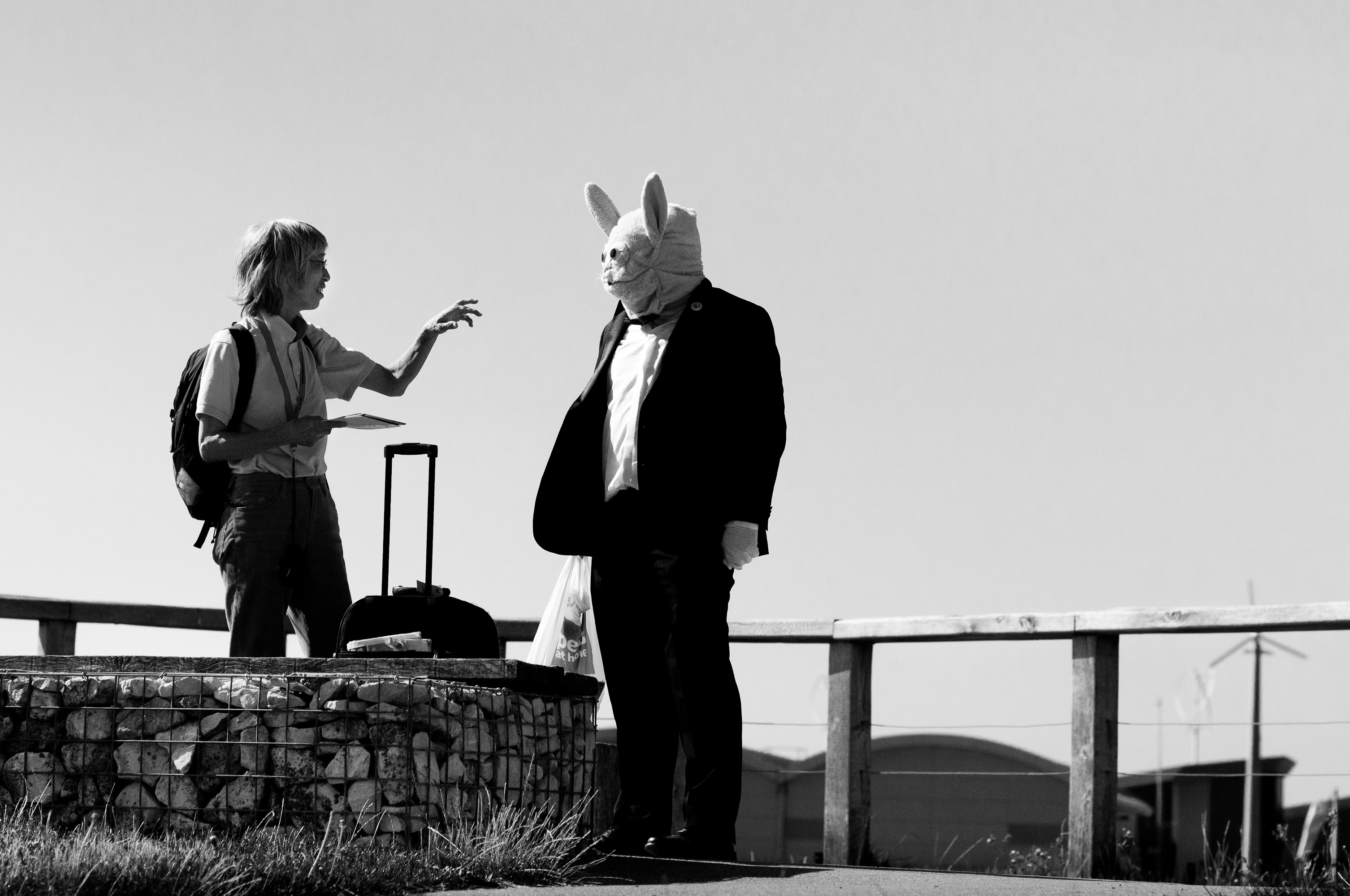 A person in a dinner suit and a white rabbit mask talks to a female tourist.