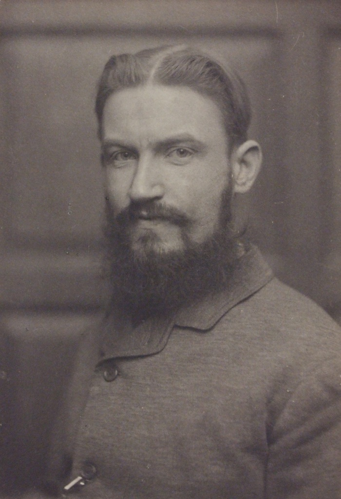 A black and white photo of the writer George Bernard Shaw. He is a white man with dark hair, swept back and centre parted. He has a moustache and a long beard. he is wearing buttoned-up jacket.