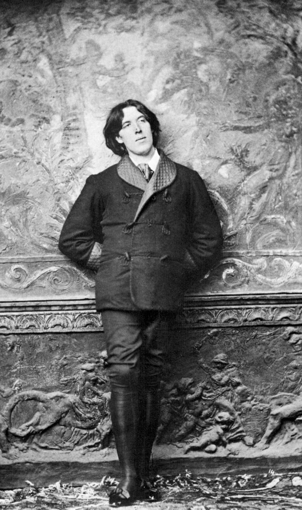 A black and white photo of the writer Oscar Wilde. He is a white man with long. dark hair parted in the middle. He is leaning against a wall wearing  a dark smoking jacket with a quilted satin collar, and dark trousers tucked into knee-length black boots.