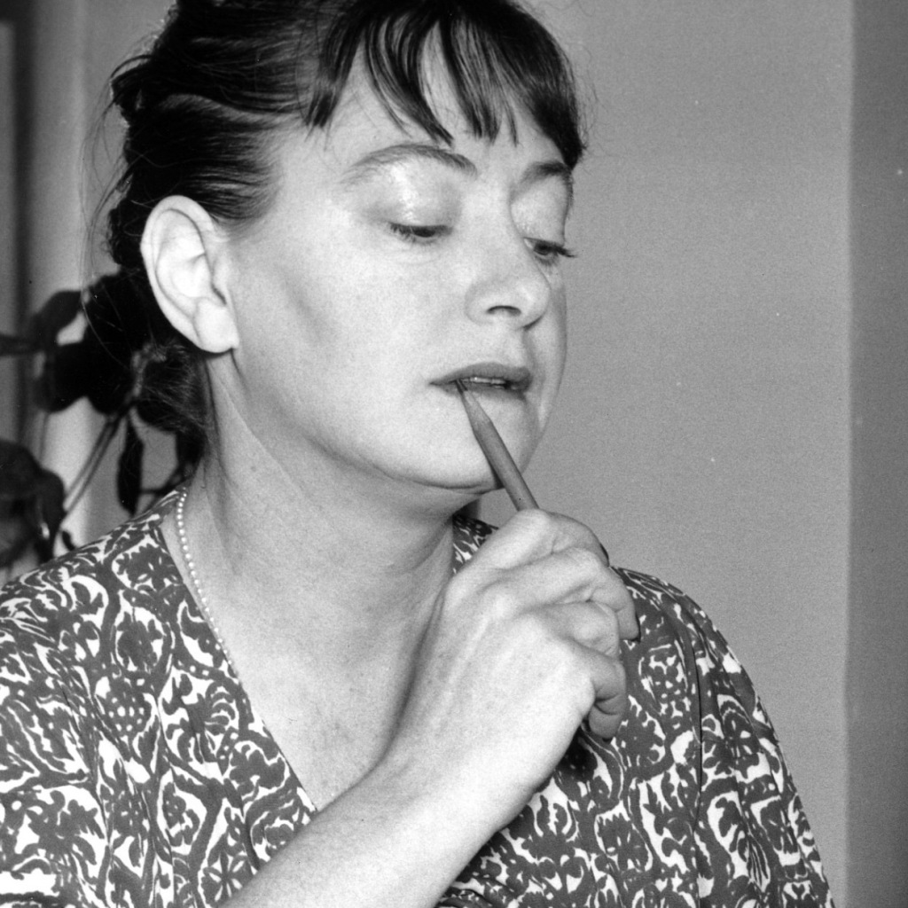 A black and white photo of the writer Dorothy Parker. She is a white woman with dark hair tied back, a fringe at the front. She is wearing a patterned blouse and is holding a pencil to her mouth as if she is thinking about what she will writer next.