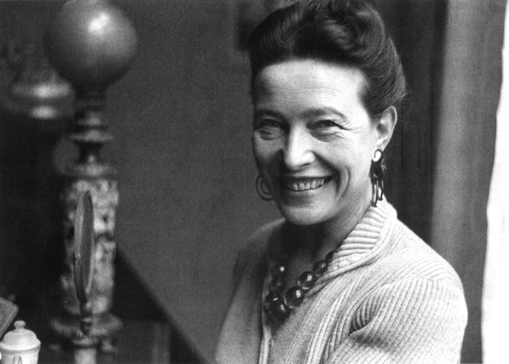 A black and white photo of the writer Simone de Beauvoir. She is a white woman with her dark hair tied up on the top of her head. She is smiling, wearing a knitted top, beads and dangling earrings.