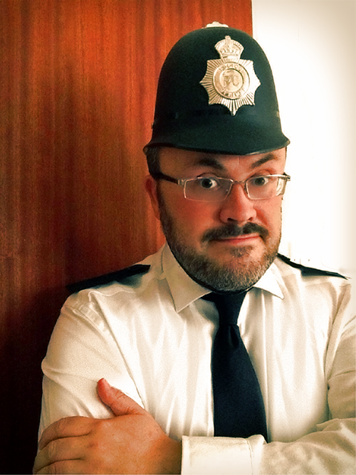 Alistair Gentry in Artbollocks Theatre: he has his arms folded and he is dressed as a police officer, except that the police helmet is much too small.