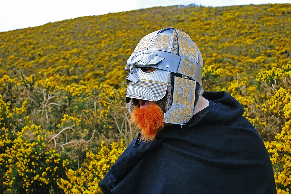 A person wearing a silver. engraved Viking helmet. They have a false ginger beard and they are shouting or screaming. In the background is a hillside covered in yellow flowering gorse.