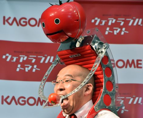 Japan's food company Kagome employee Shigenori Suzuki tries to eat a tomato which is provided from the newly developed tomato dispenser for marathon runner