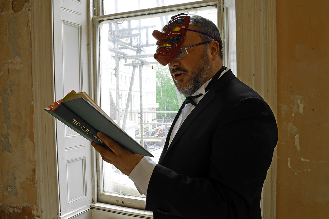Alistair Gentry performing Quid Pro Quo in a grand but dereilict room. he is wearing a dinner suit, bow tie and a Japanese Tengu mask with a read face. He is reading from a book called The Gift.