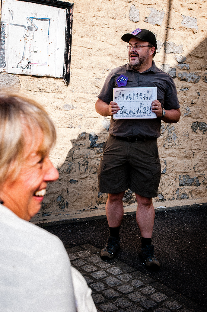 Alistair Gentry in The Portland Office for Imaginary History: dressed in a khaki uniform with shorts and a cap, he stands in front of a stone wall showing a diagram of various plants. In the foreground, a woman is looking on and laughing.