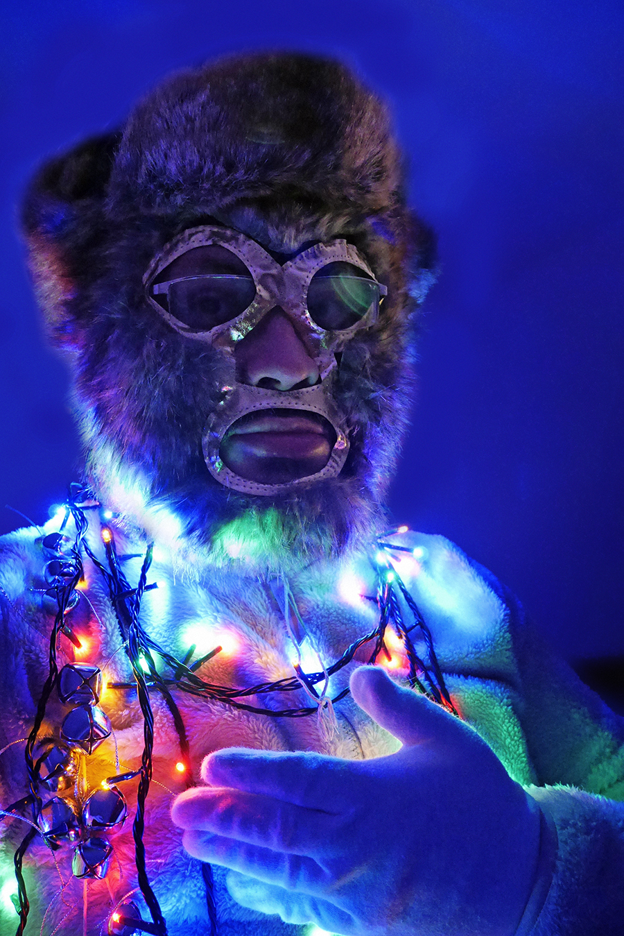 Alistair Gentry as Colonel Robin. A brown fur mask with gold trim and holes for the eyes, nose and mouth- a white fur body, white cotton gloves, and he is wrapped in strings of sleigh bells and coloured Christmas lights.