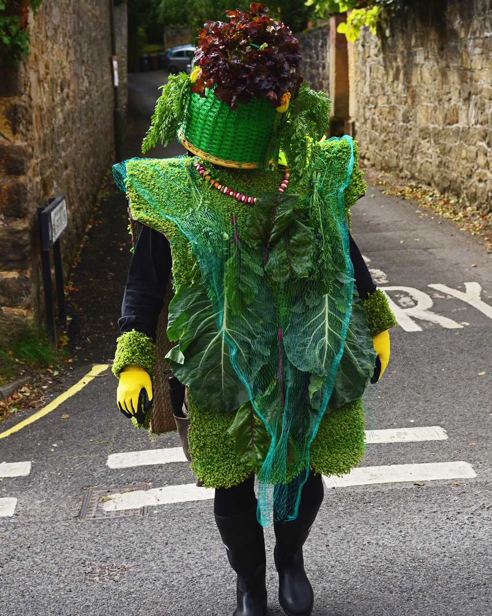 A green, full body  costume made of wicker, green grocer's artificial grass, and fresh plants and vegetables.