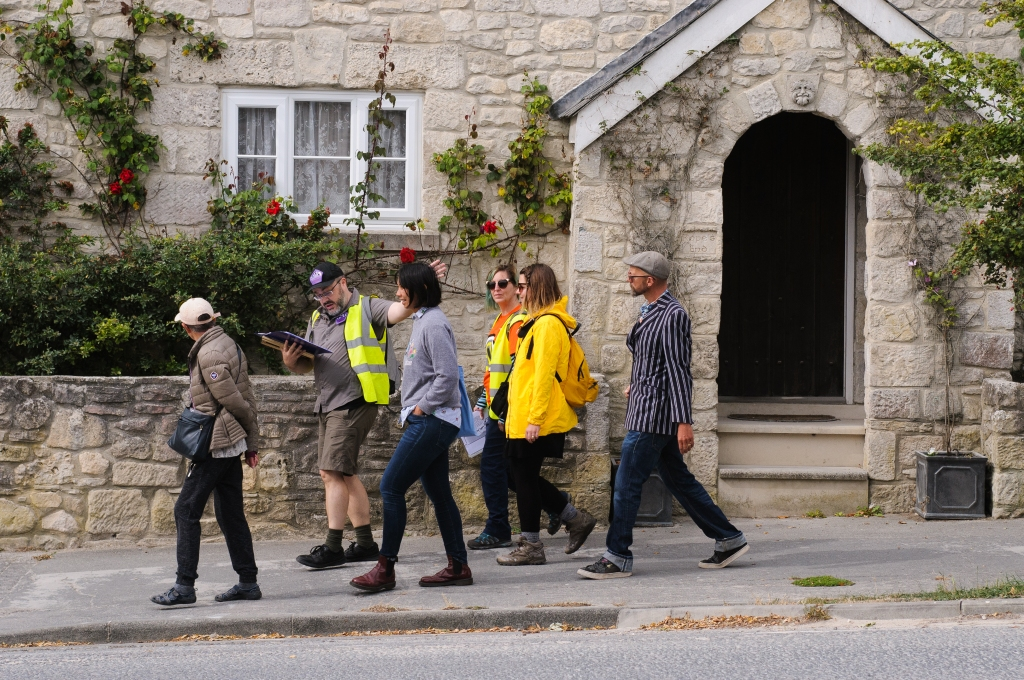 Alistair Gentry and members of the audience on a tour for the Portland Office for Imaginary History. They are walking in front of a beige stone house with an arched porch entrance. Red roses are growing over the house.