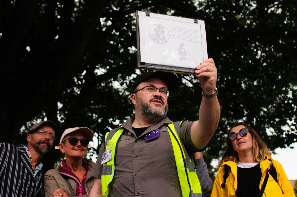 Alistair Gentry and members of the audience for The Portland Office for Imaginary History. They are all looking through a frame at something out of shot. Alistair is wearing a khaki ranger's uniform, a black hat and a high visibility yellow vest.