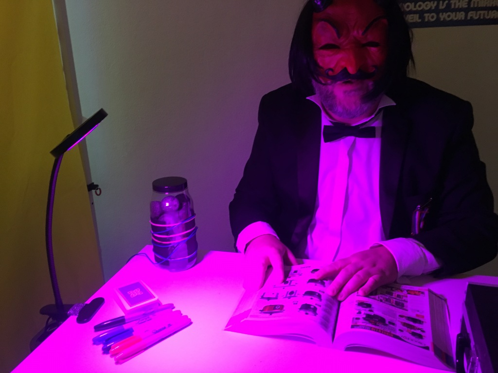 Alistair Gentry performing Hunter Moon. He is sitting at a desk; on its surface are a jar wrapped in wires containing black objects, a bright and unpleasant magenta light, a deck of cards, Sharpie markers and an open paper Argos catalogue. Alistair is wearing a dinner jacket, a bow tie, a red devil mask and a black wig.