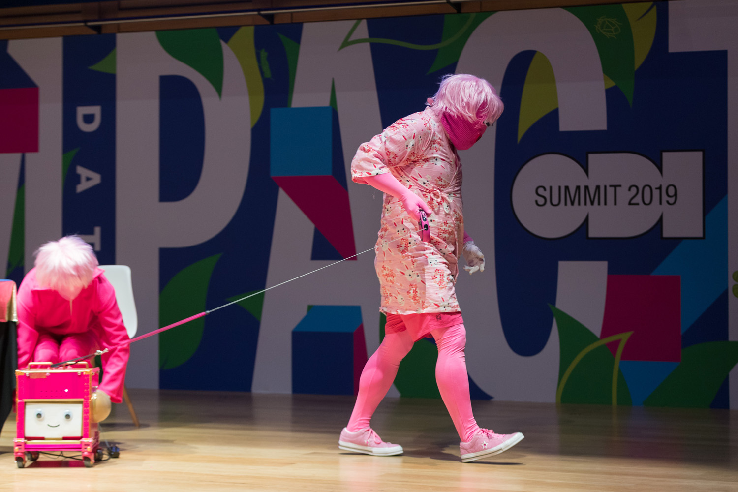 A person dressed in pink, with a pink mask, leading a small pink robot with a smiling face from a stage.