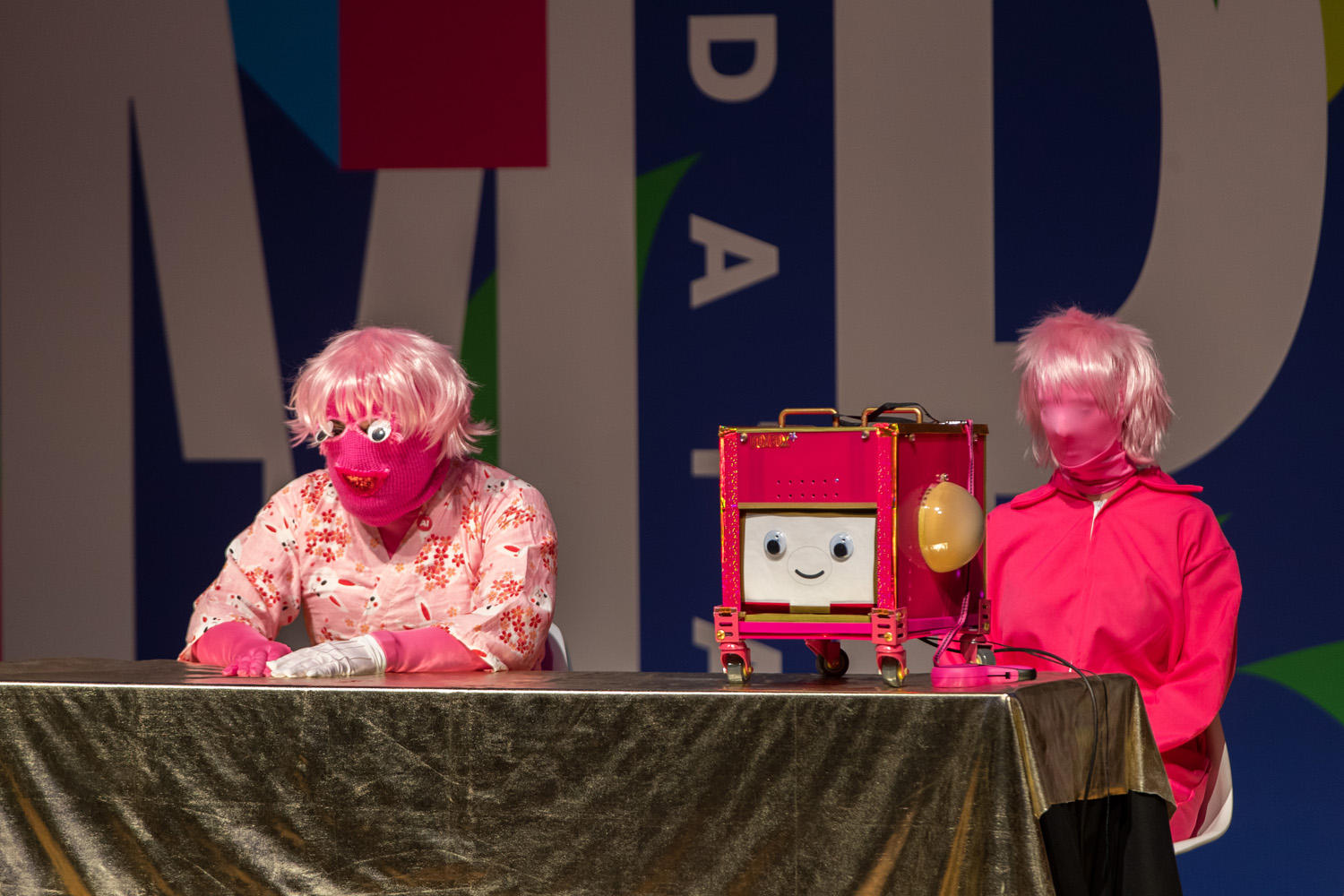 Two people wearing pink masks and wigs, one wearing a pink kimono and the other wearing a pink jumpsuit, sitting at a table with a gold tablecloth. On the desk is a cubic robot on wheels, with a smiling face.
