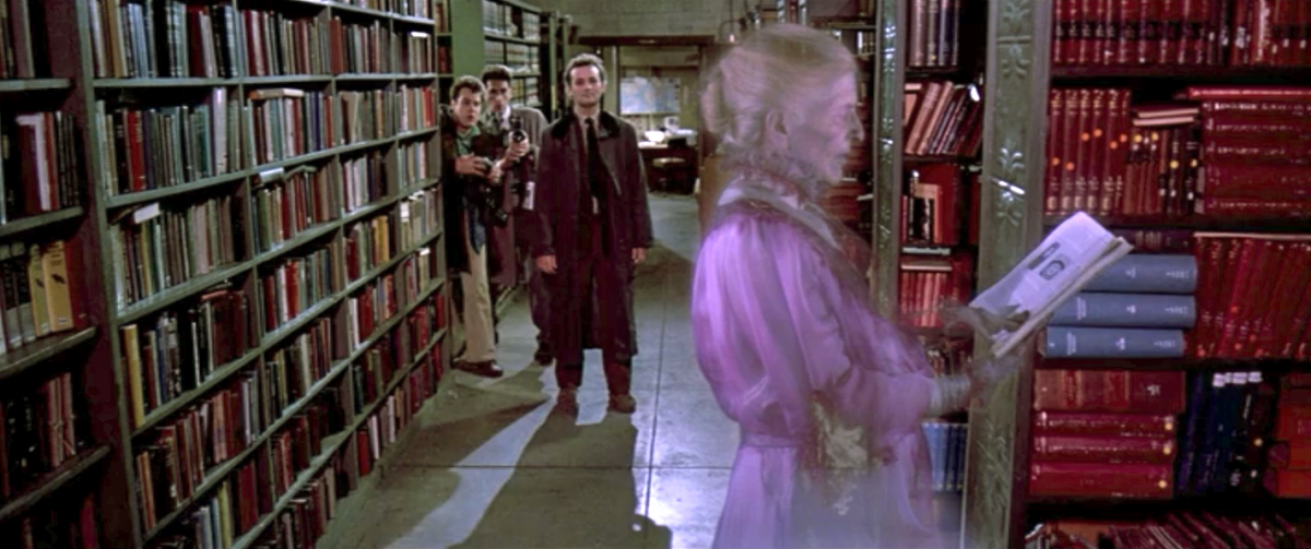 A ghost in a mauve Victorian dress reads a book in a public library, while the Ghostbusters watch.