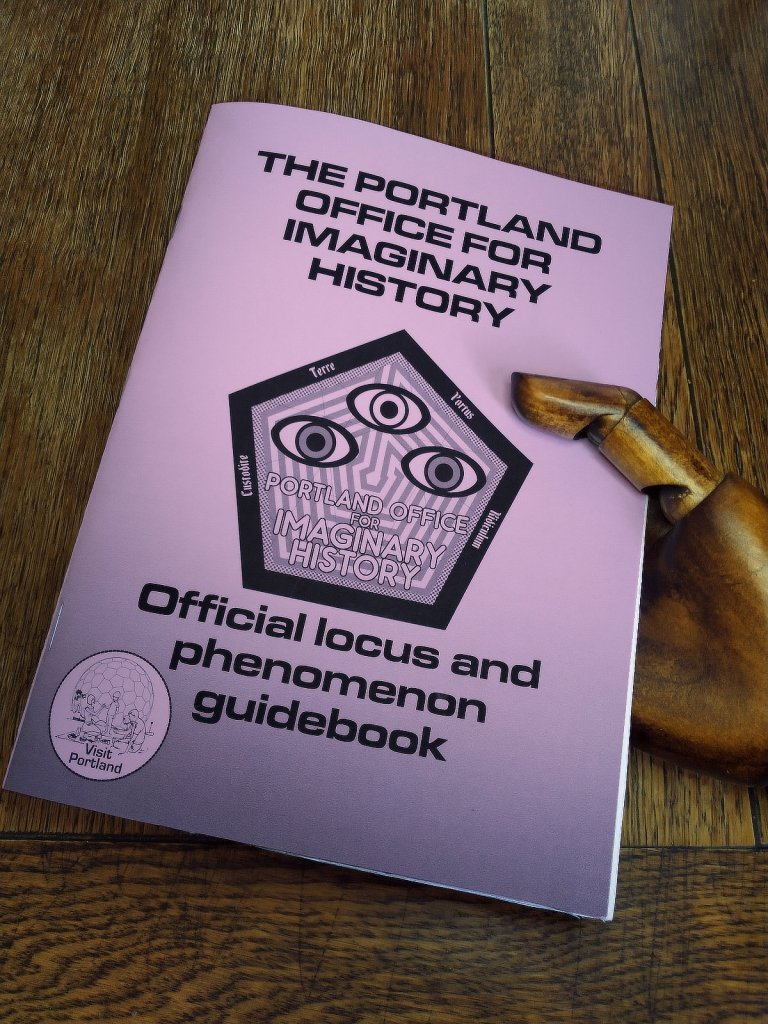 A wooden hand holding a Portland Office for Imaginary History Official Locus and Phenomenon Guidebook with a lilac cover.