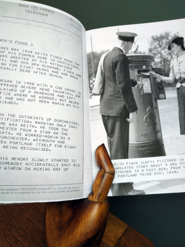 Wooden hand holding a booklet open at a page showing a photo of a man at a post box on the right, with text on the left page.