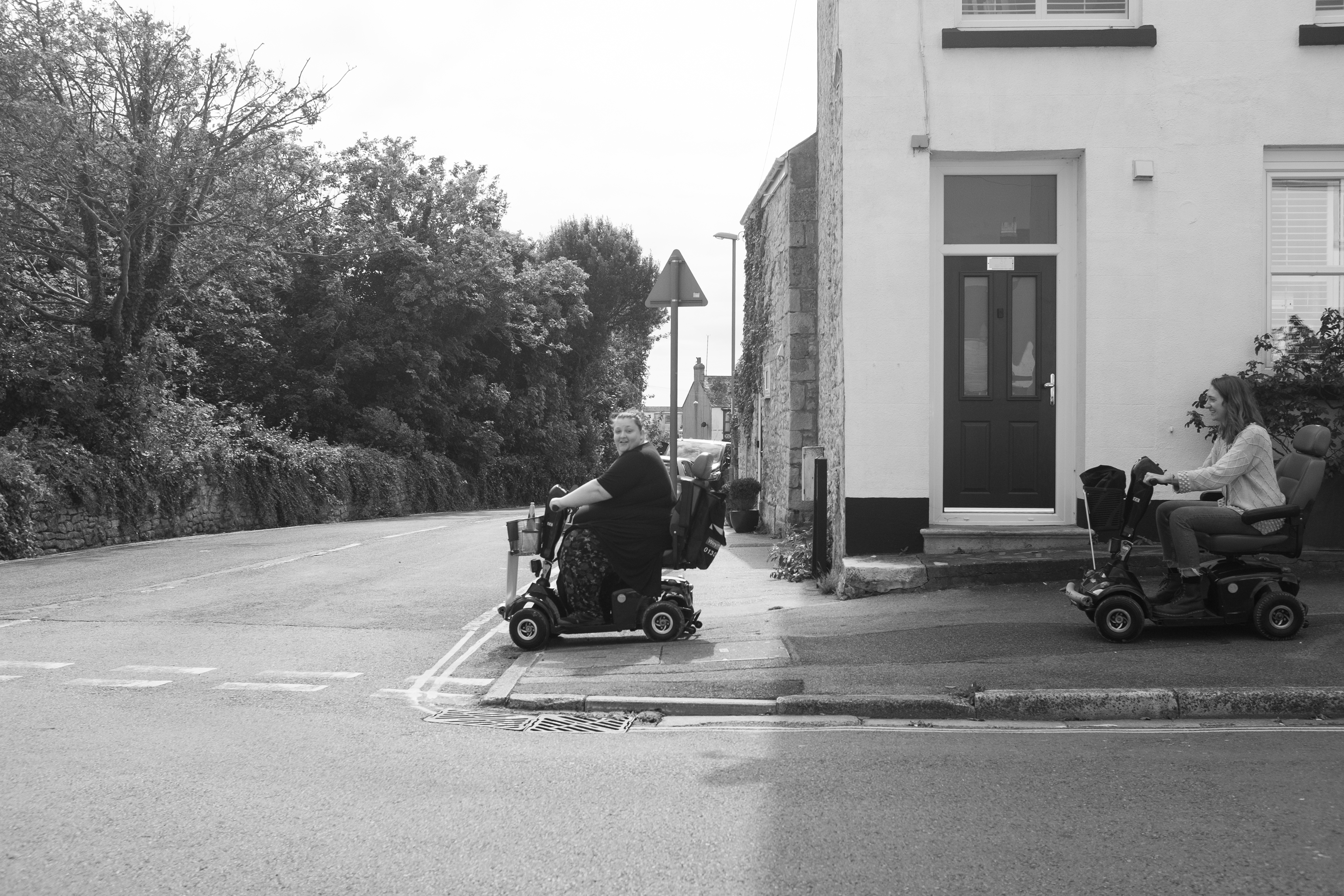 A black and white of two people on mobility scooters, about to cross a road.