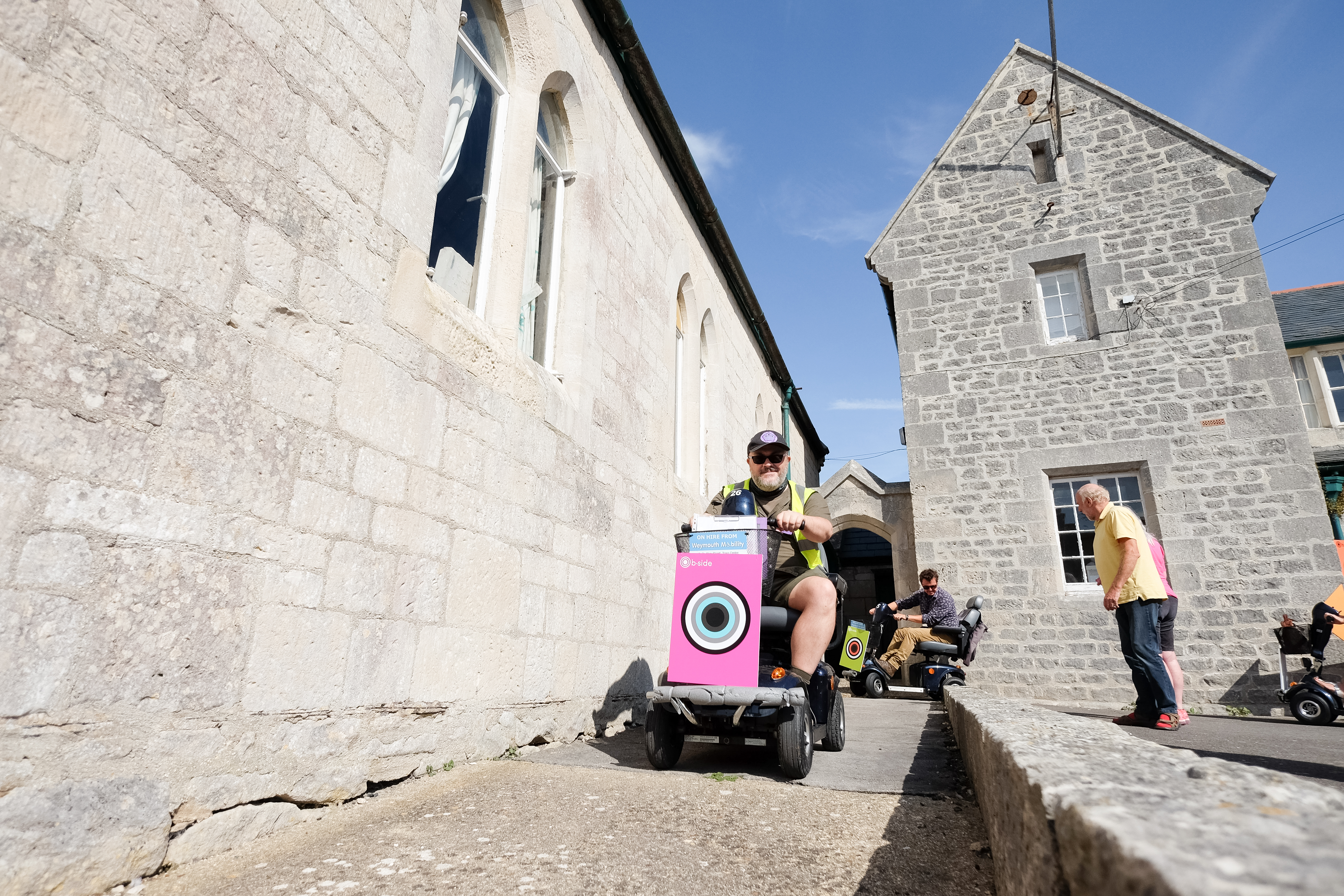 Alistair Gentry dressed as an Imaginary History ranger with a hi-vis jacket and cap, with mobility scooter users beside an old stone building.
